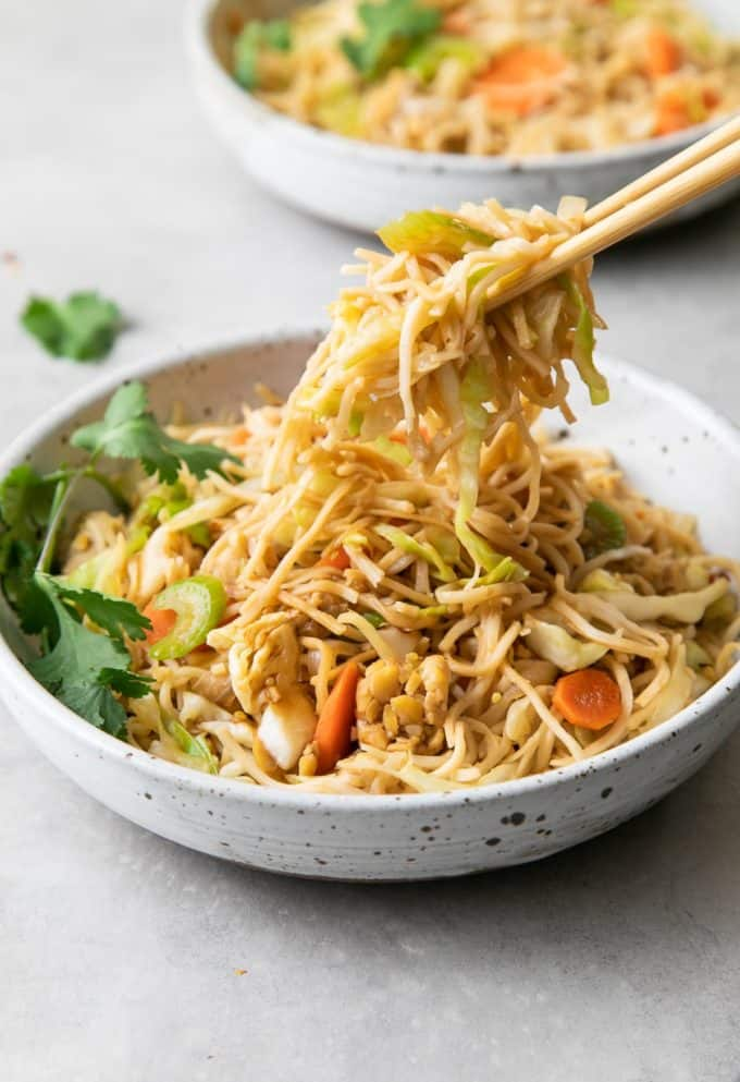 Chopsticks scooping up chow mein from a while bowl