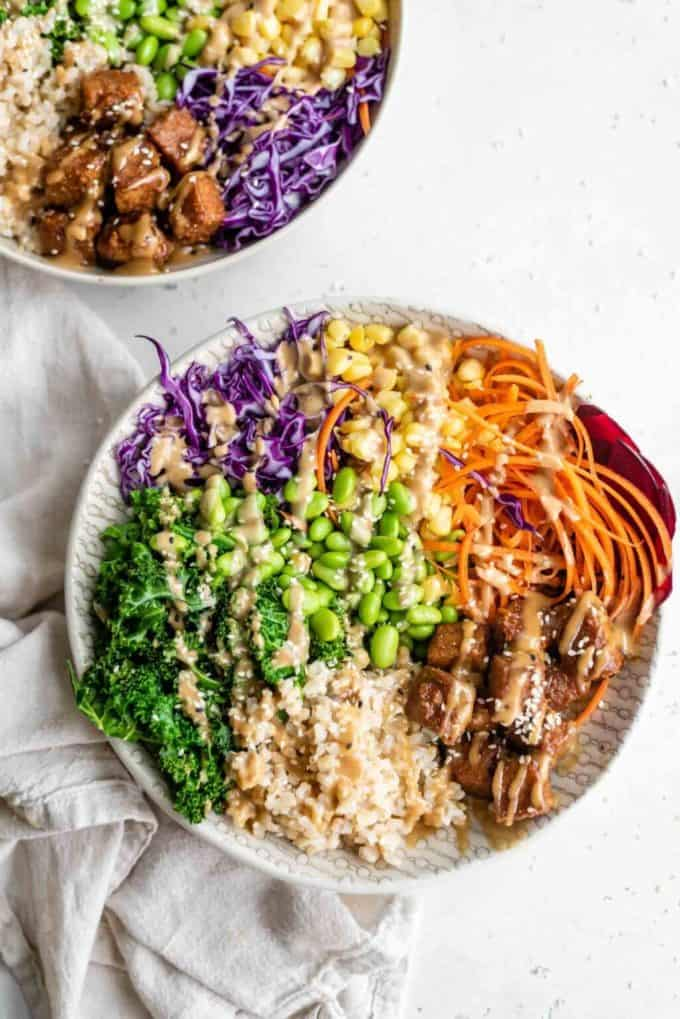 A buddha bowl with rice, vegetables and tempeh in it
