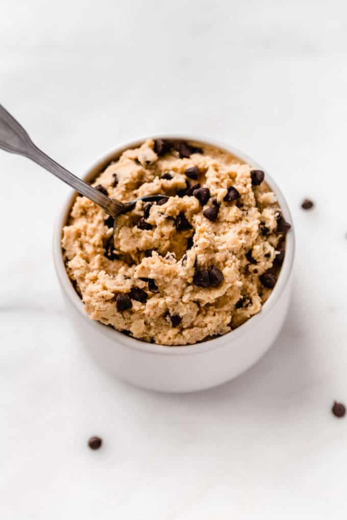 chickpea cookie dough in a small white bowl with a spoon in it
