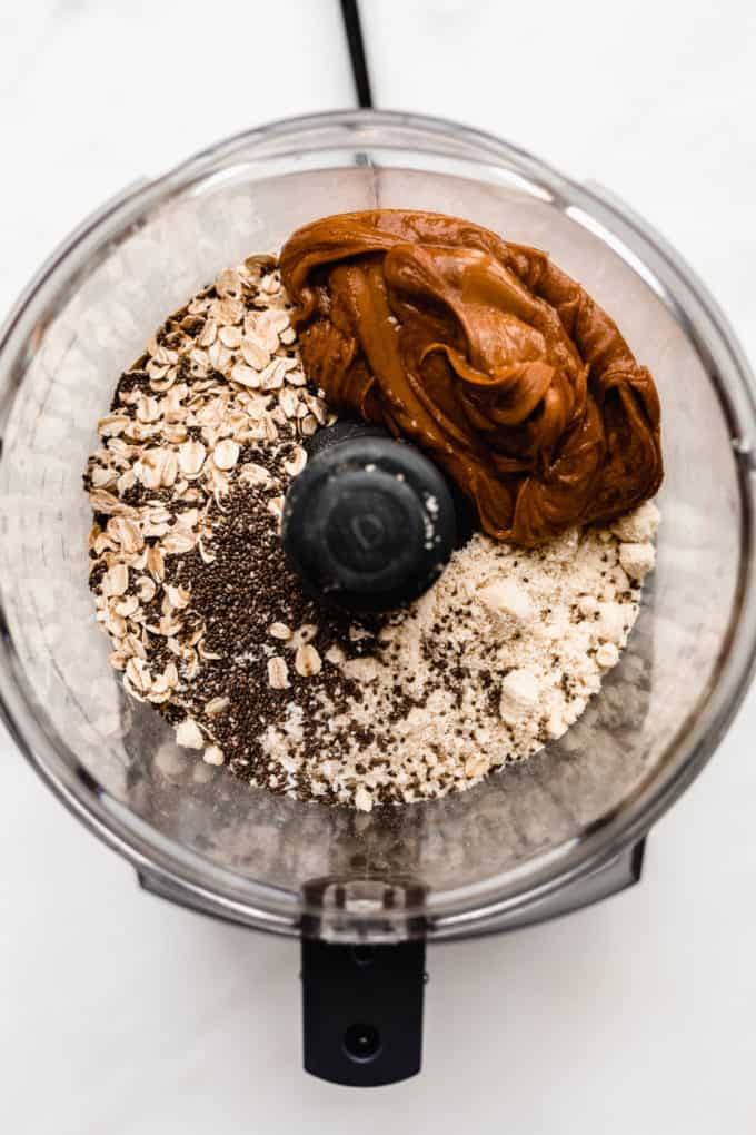 A food processor with oats, almond flour, chia seeds, peanut butter and maple syrup