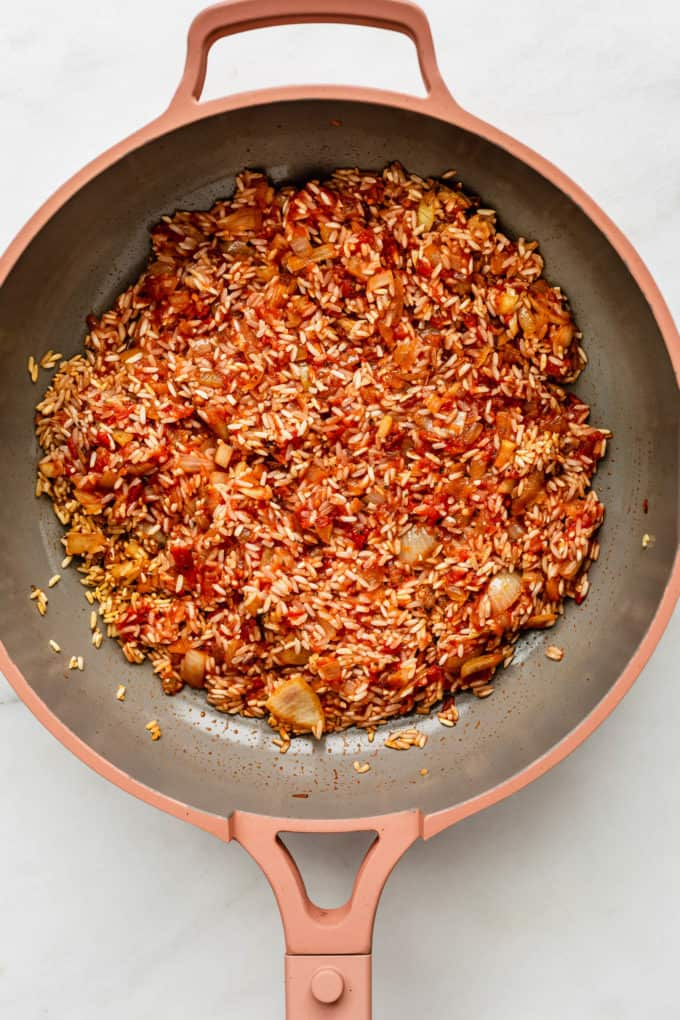 A pan with crushed tomatoes, rice and onions in it