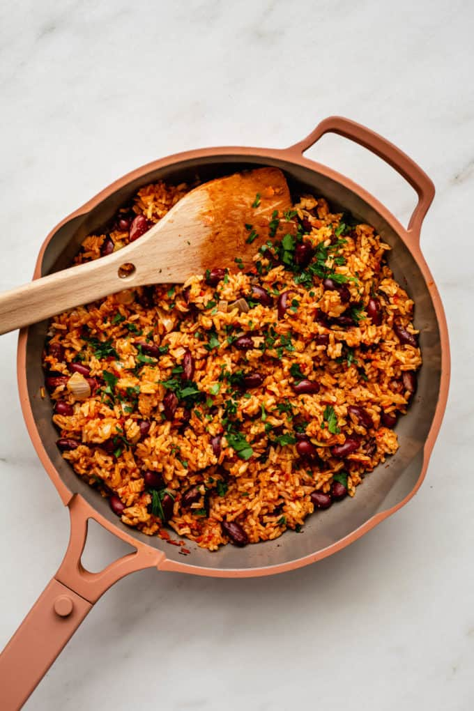 a pan of spanish rice and beans topped with parsley