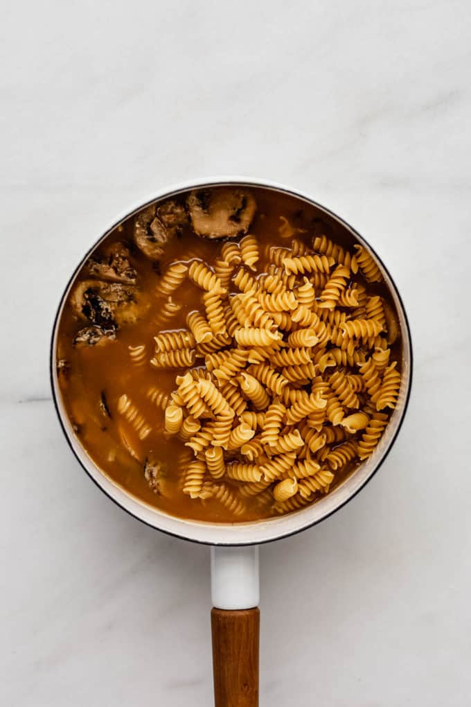 A white pot with mushrooms, broth and uncooked pasta in it