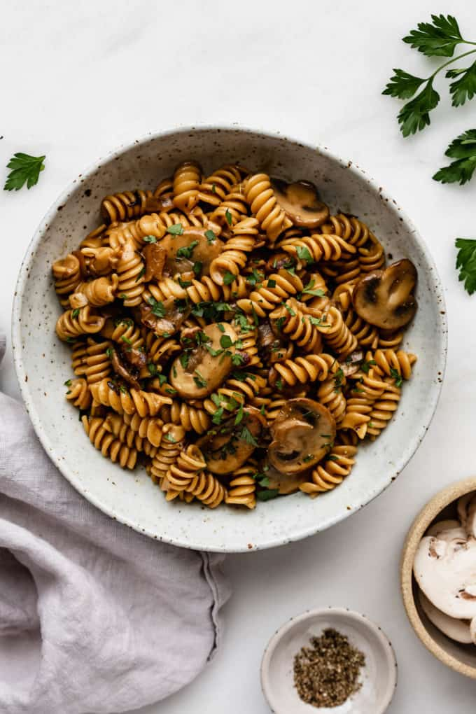 A bowl of mushroom stroganoff with a grey napkin and parsley on the side