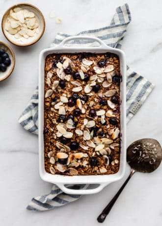 A baking dish with blueberry baked oatmeal in it on a blue napkin
