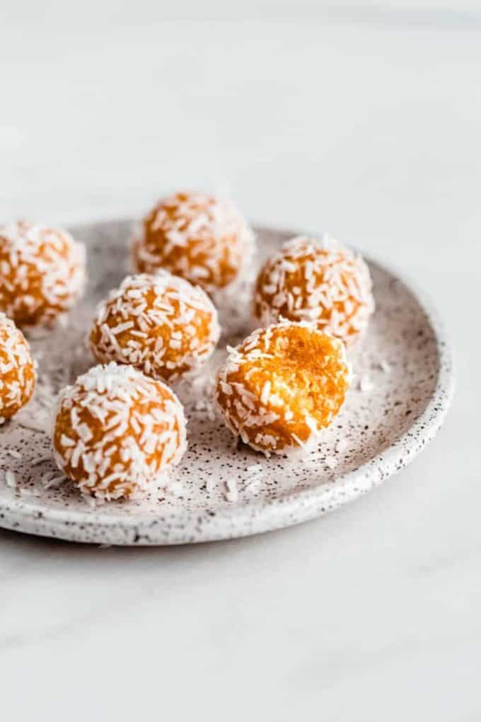 Apricot energy balls topped with coconut on a white speckled plate