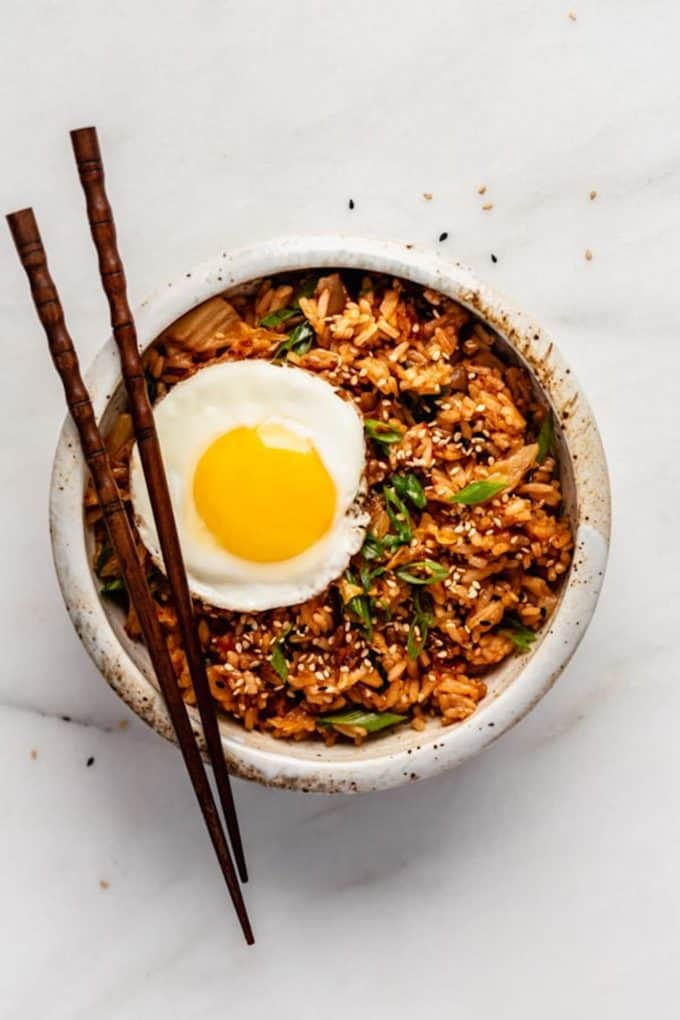 kimchi fried rice with a fried egg on top in a bowl with chopsticks on the side