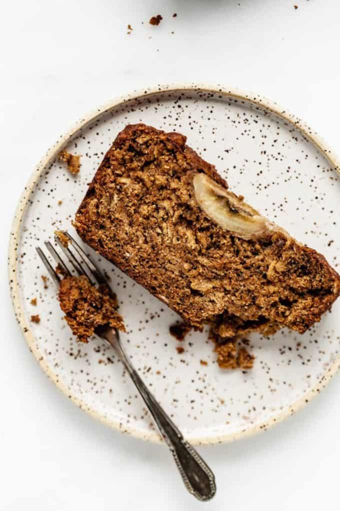 vegan banana bread on a white speckled plate with a fork