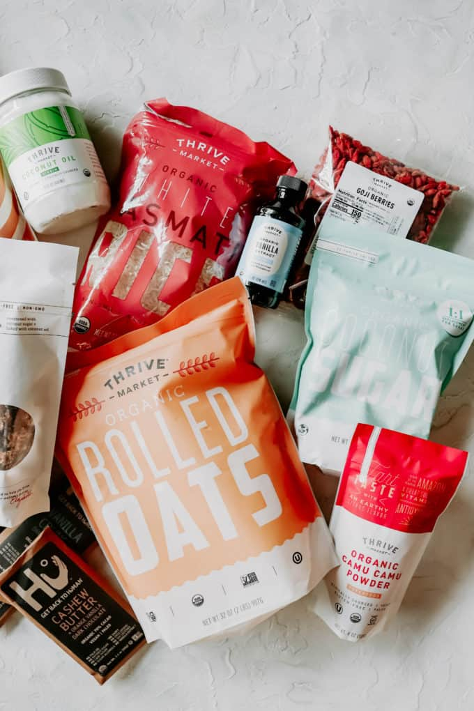 A flat lay of health food products including rolled oats, chocolate, coconut sugar and rice