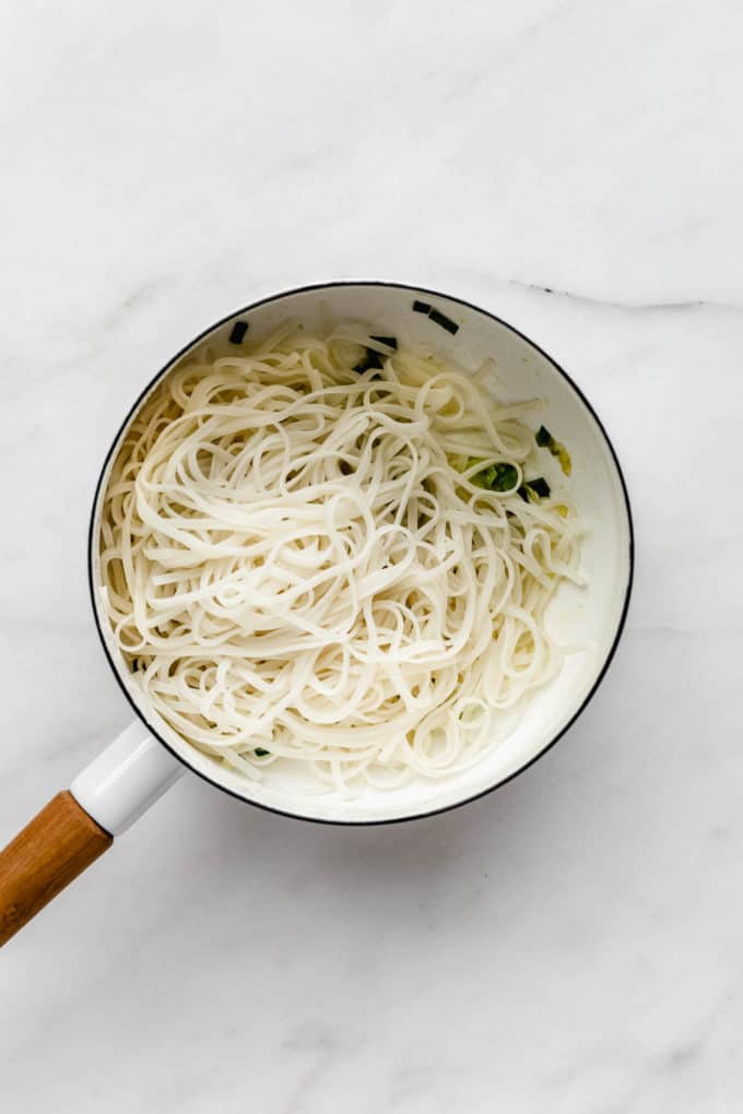 A white pot with rice noodles in it