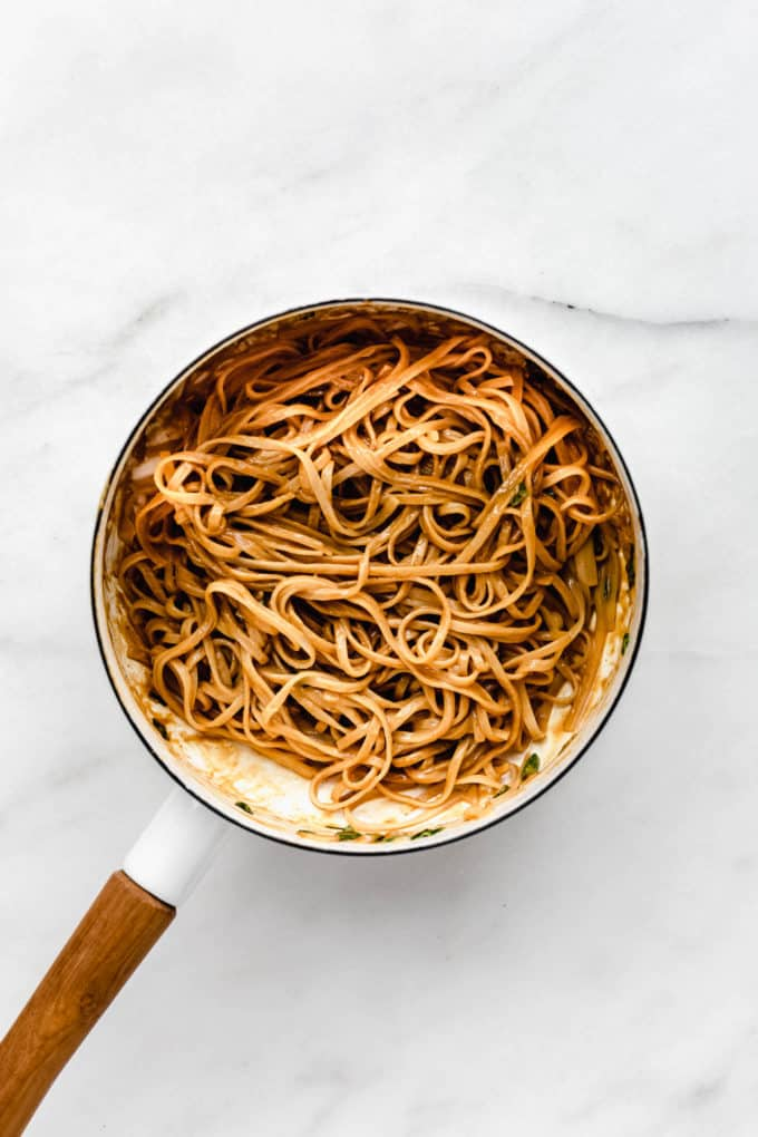 Peanut butter noodles in a white pot with a wood handle