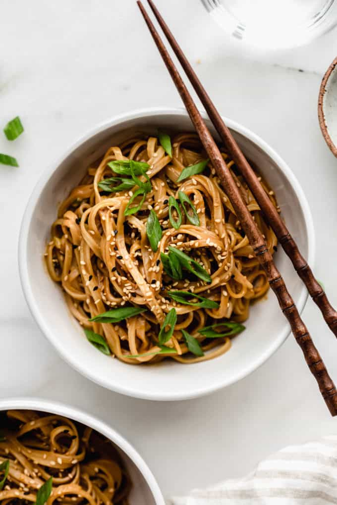 A bowl of peanut butter noodles with wooden chopsticks on the side