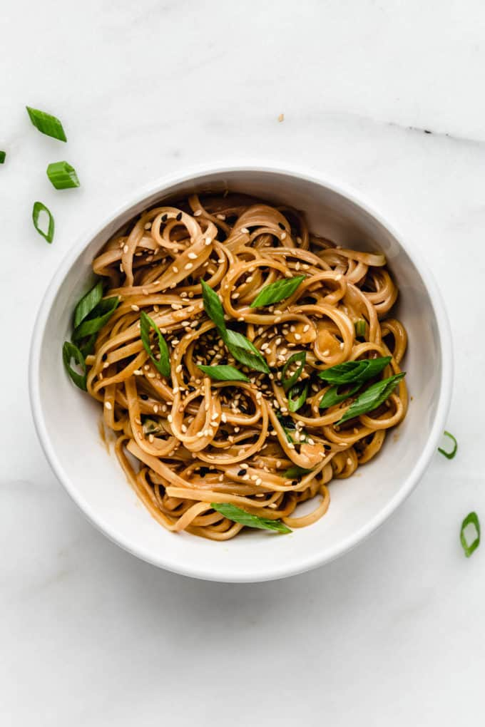 Rice noodles with peanut butter sauce in a white bowl