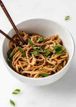 Peanut butter noodles in a white bowl topped with green onions
