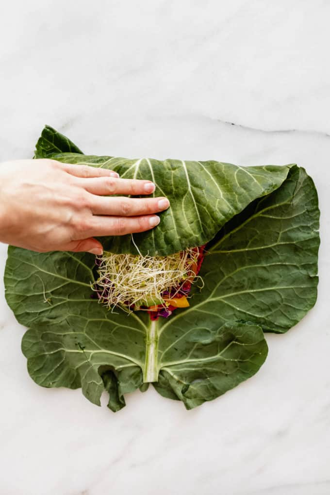 A hand folding a collard green with vegetables inside