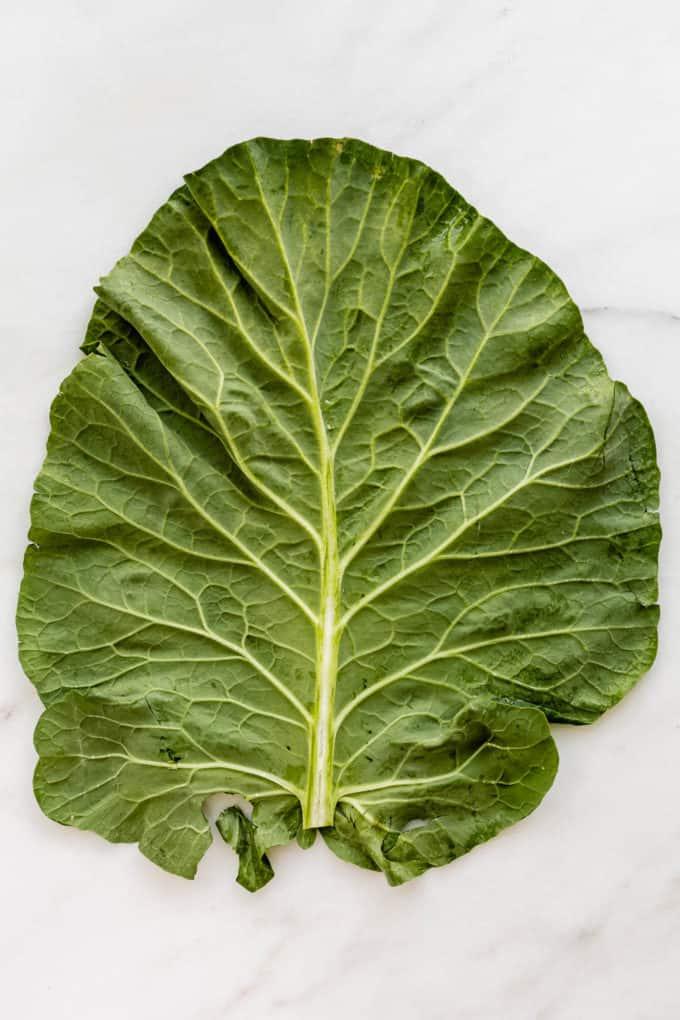 A collard green leaf on a marble board