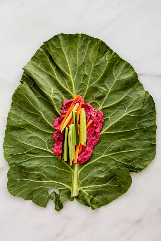 A collard green leaf with beet hummus and cucumber on it