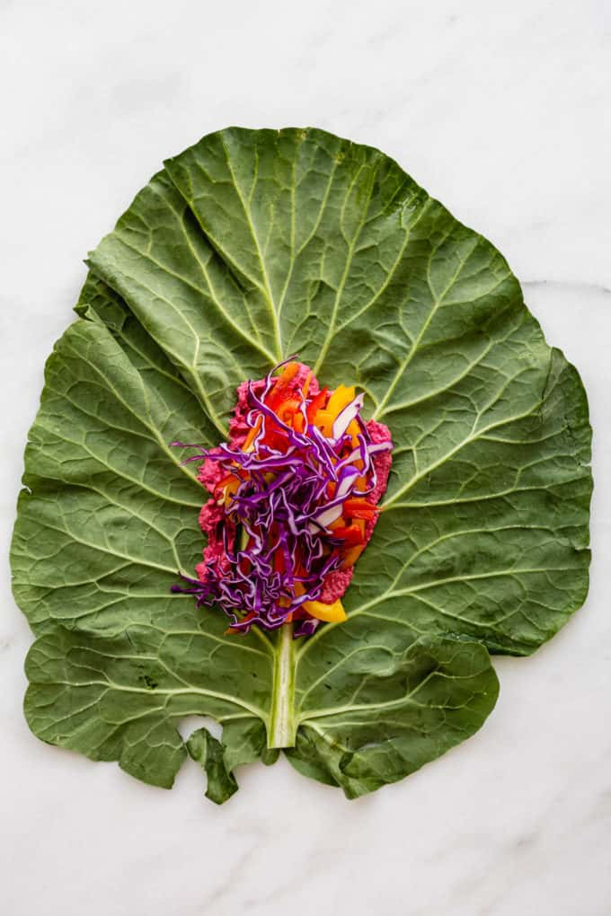A collard green leaf with purple cabbage on it