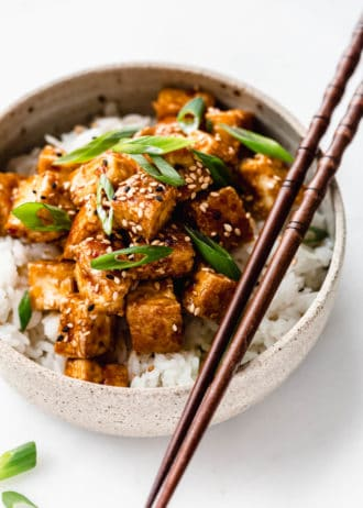 teriyaki tofu in a ceramic bowl with wooden chopsticks