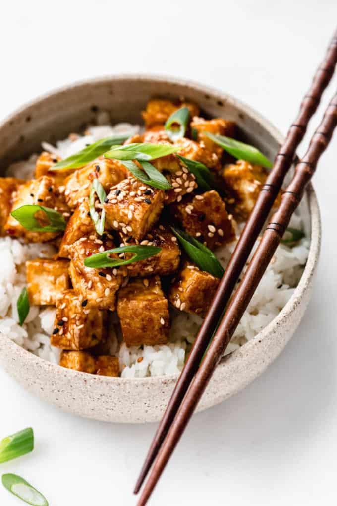 teriyaki tofu in a ceramic bowl with wooden chopsticks