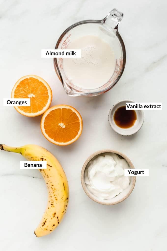 Almond milk, Orange, banana, yogurt and vanilla laid out on a white board