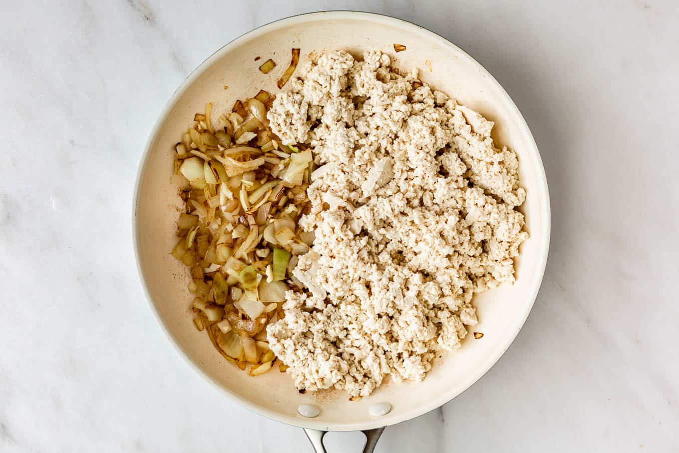 crumbled tofu, onions and garlic in a white pan