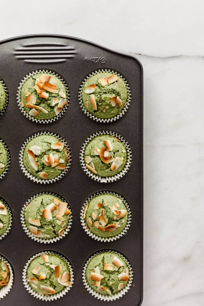 baked matcha muffins topped with coconut in a muffin pan