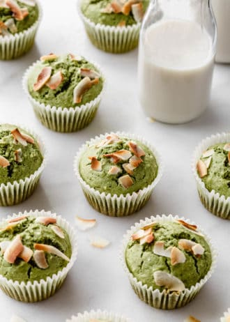 matcha coconut muffins on a marble counter with a jar of milk