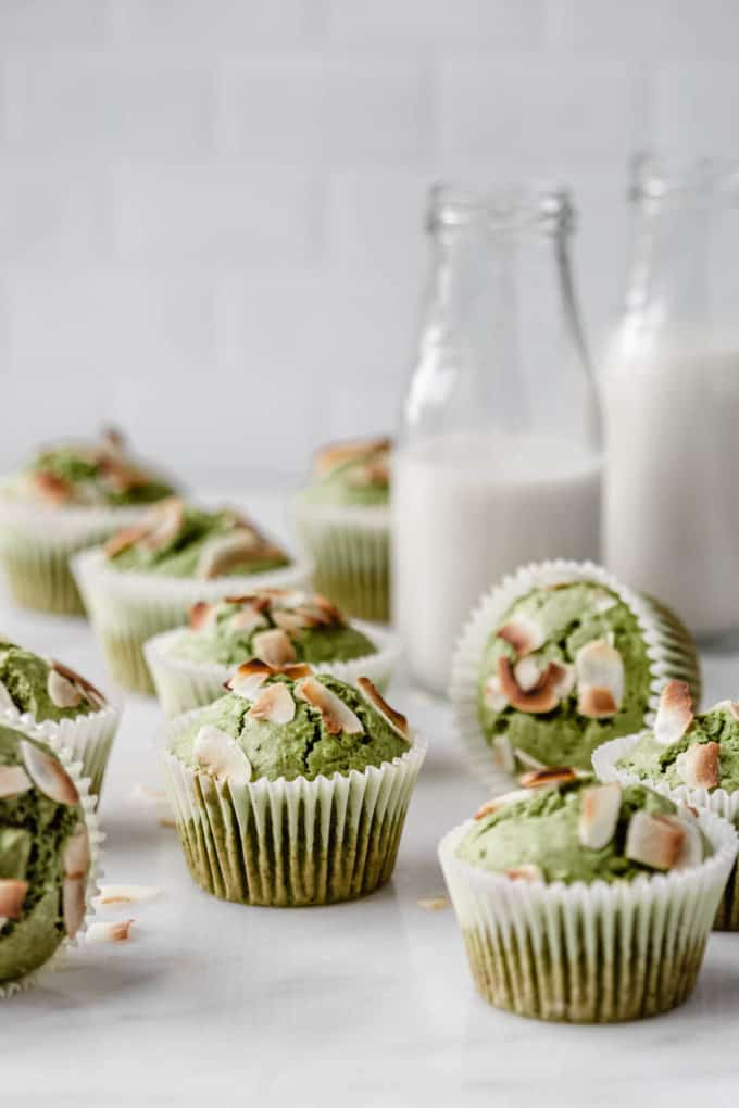 matcha coconut muffins with 2 jars of milk in the back