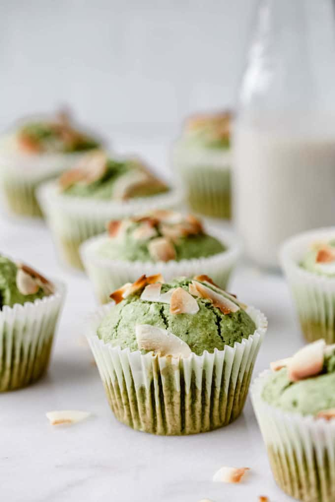 a matcha coconut muffin topped with coconut flakes