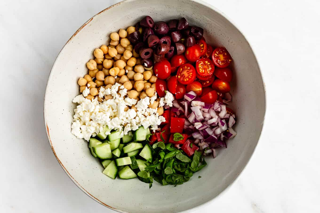 A bowl of vegetables, chickpeas and feta cheese
