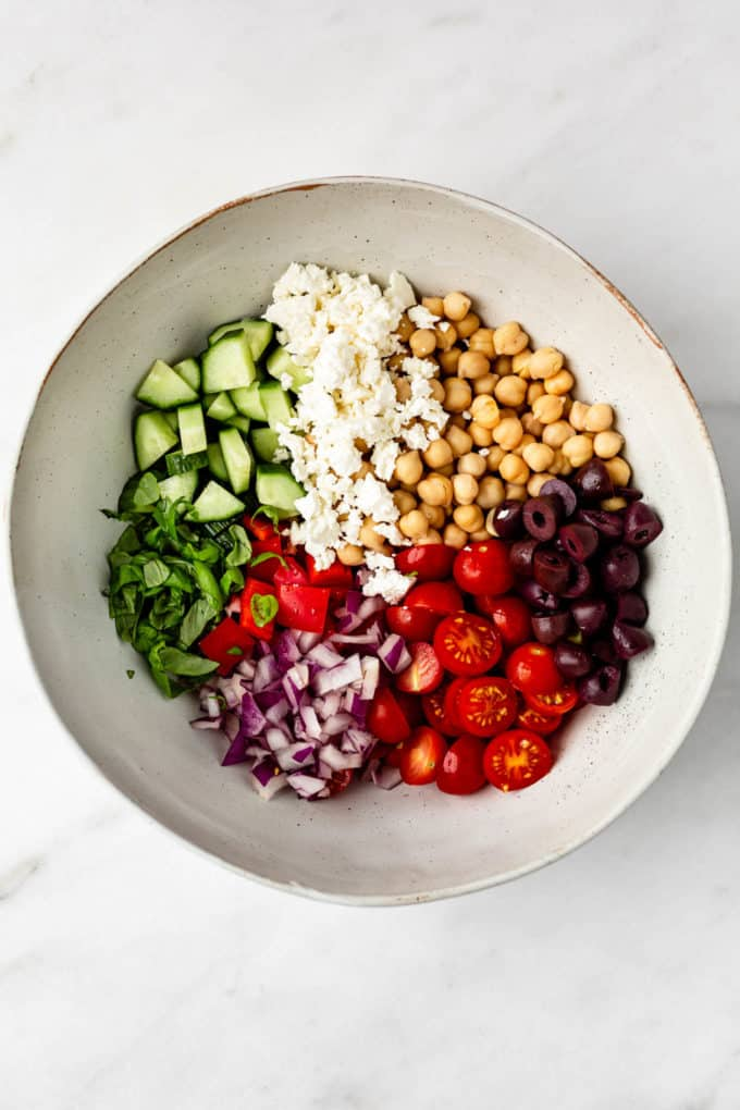 Chickpeas, feta, olives, tomatoes, cucumbers and red peppers in a bowl