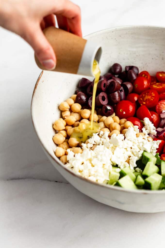 a hand pouring dressing into a bowl of salad
