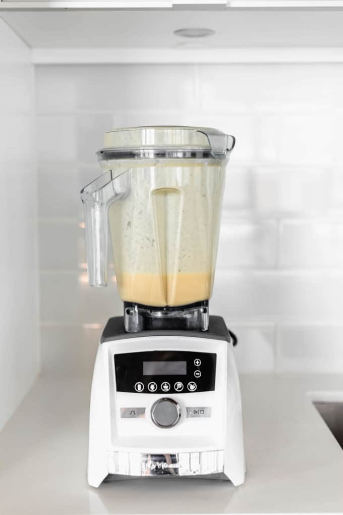 A white blender with orange smoothie in it