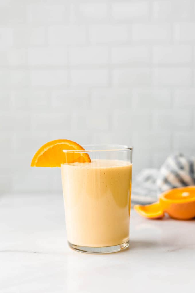 an orange smoothie on a white marble counter with a blue striped napkin