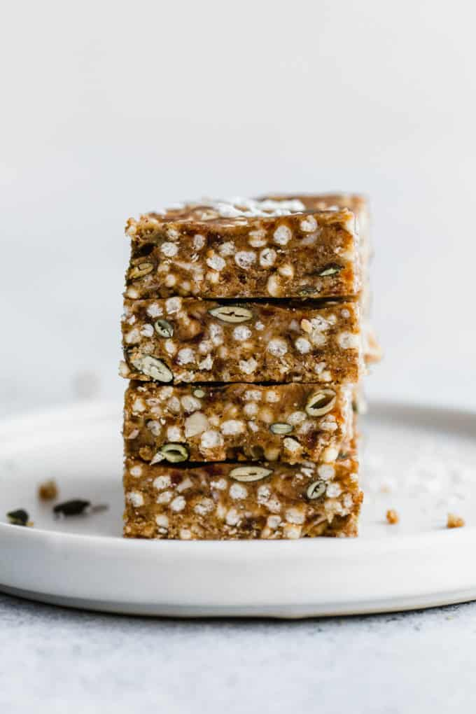 four puffed quinoa bars stacked on a white plate