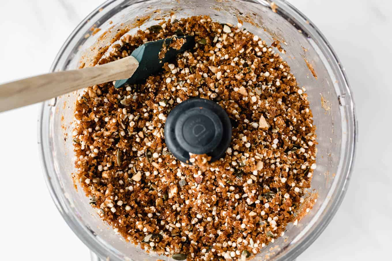 A food processor with quinoa date and nut bars dough in it