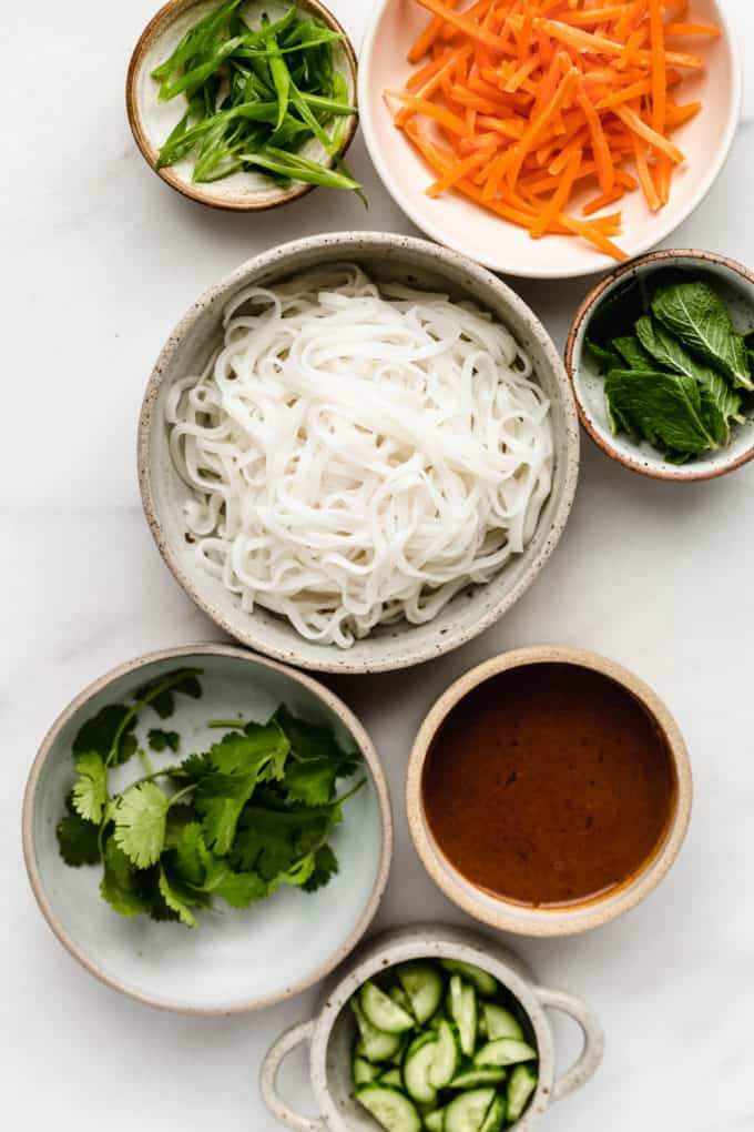 bowls filled with ingredients to make spring rolls