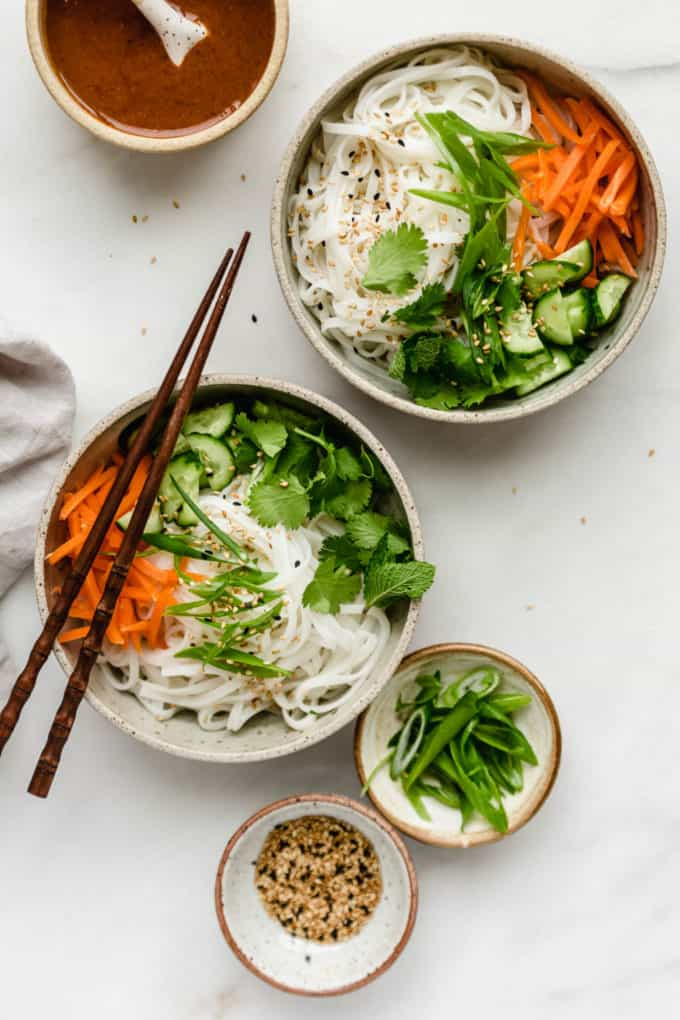 two bowls of rice noodles and vegetables with chopsticks