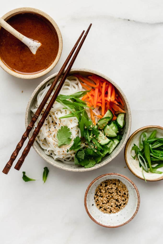 A spring roll noodle bowl with almond butter sauce on the side