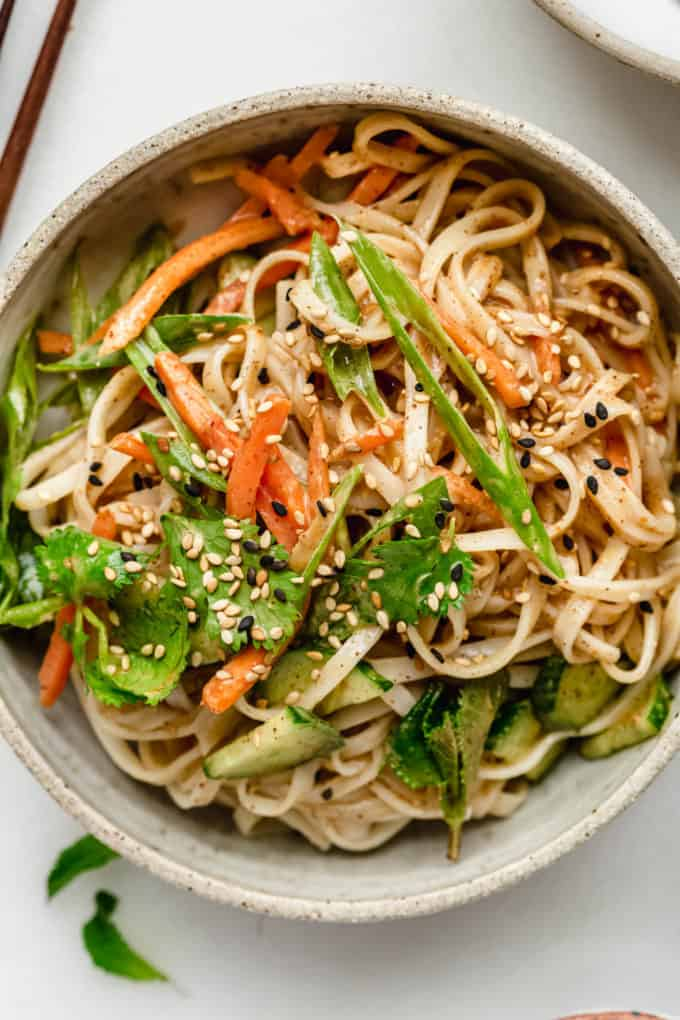 noodles and vegetables in a bowl topped with sesame seeds