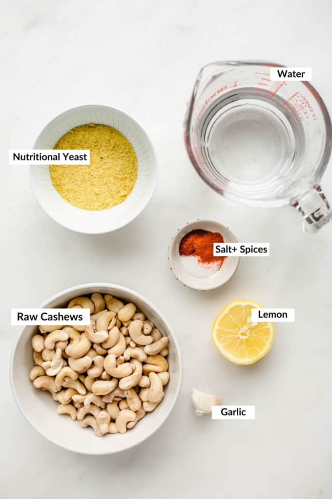 raw cashews, nutritional yeast, spices and water on a marble board