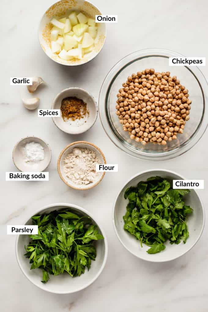 herbs, chickpeas, spices, onions, flour, baking soda and garlic laid out on a marble board
