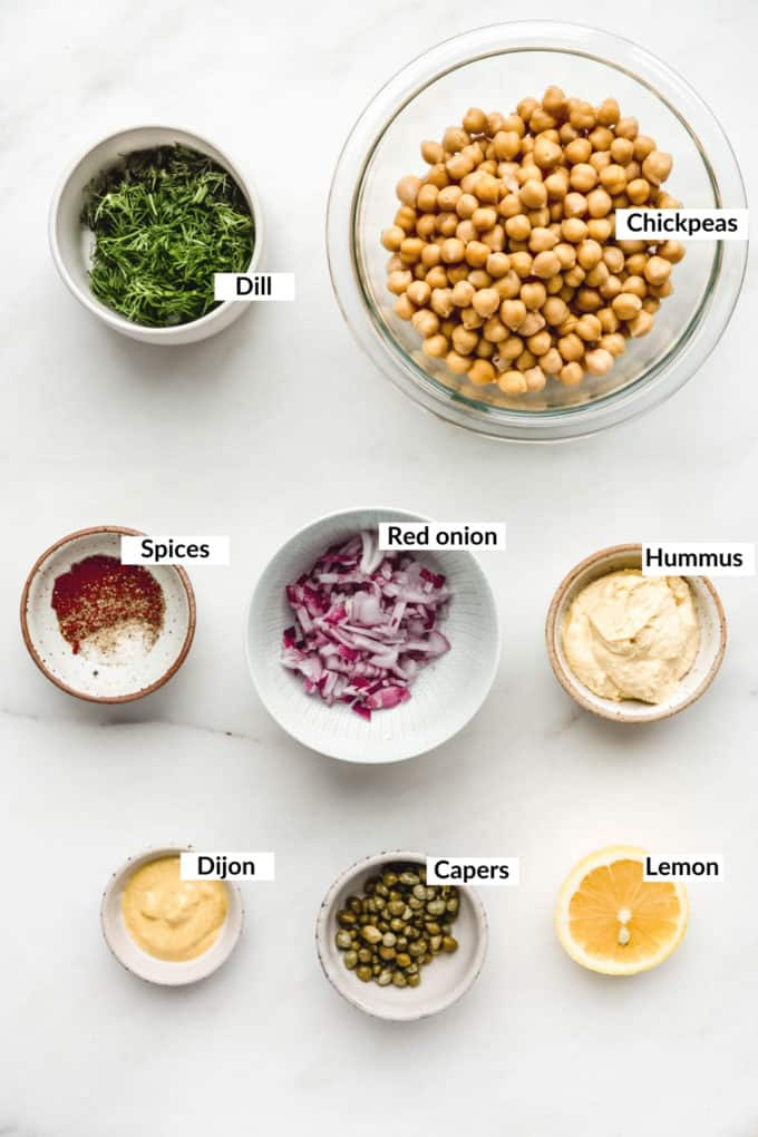 Ingredients for smashed chickpea salad sandwich laid out on a marble board