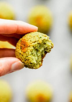 a hand holding a baked falafel ball with a bite taken out of it