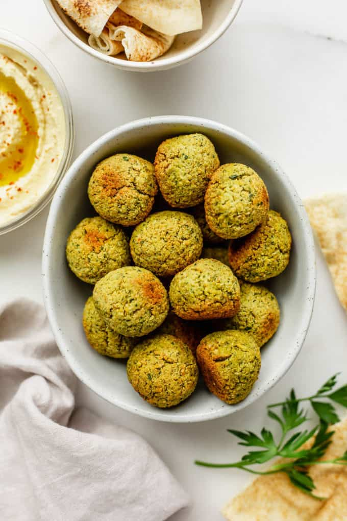 A bowl of baked falafel with pita and hummus on the side