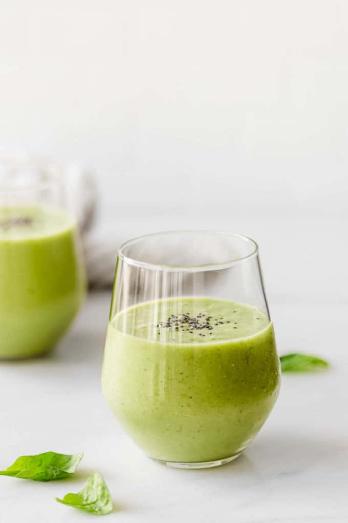 Two glasses with green smoothie in them topped with chia seeds
