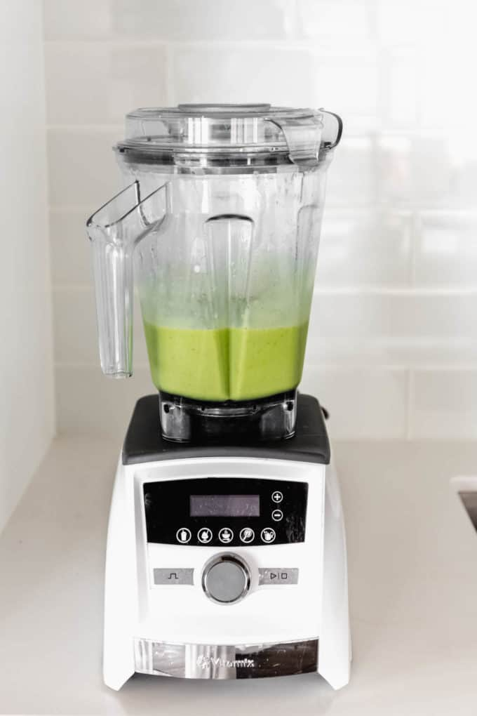A white blender with a green smoothie in it