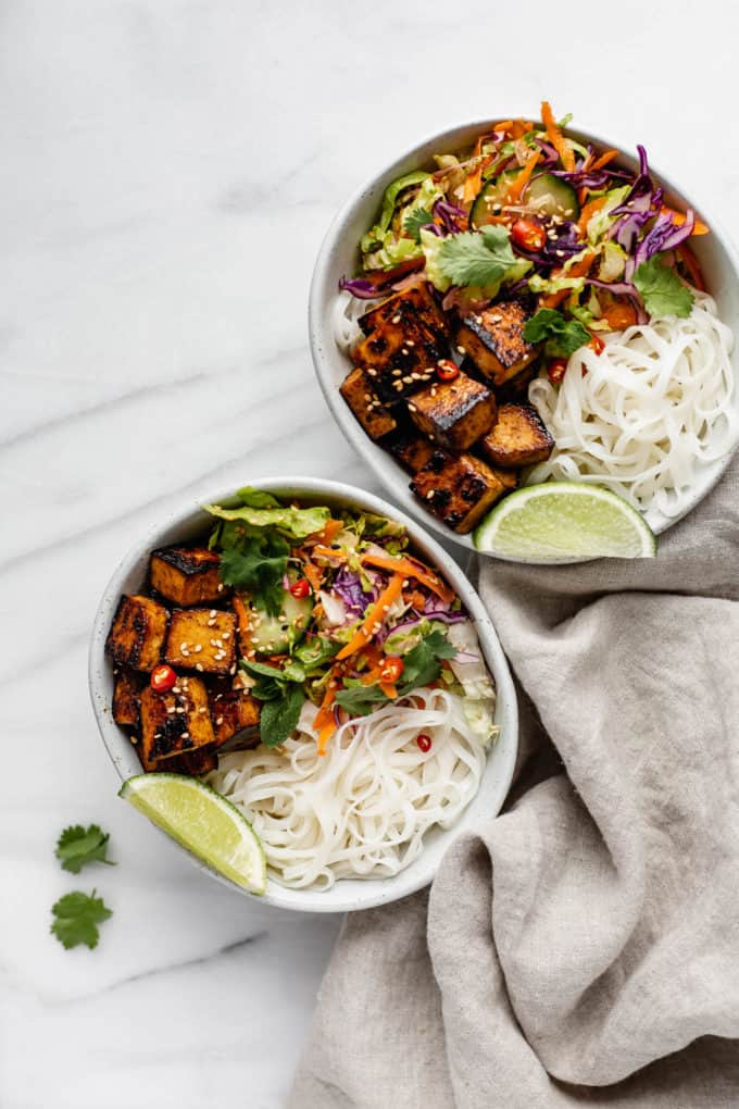 Two Vietnamese noodle bowls on a marble counter