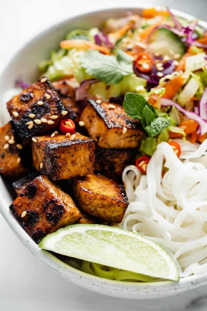 lemongrass tofu, a lime, rice noodles and salad in a bowl